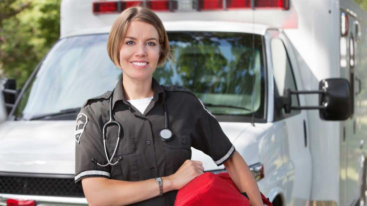 Emergency Medical Technician standing outside ambulance
